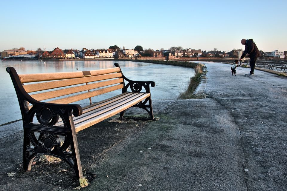Frozen bench on Emsworth Quay with dog walker